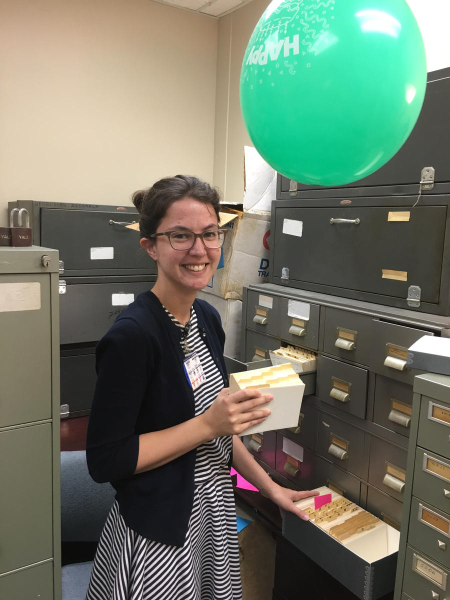 Archives Intern Kahlee Leingang packing up Department of Neurosurgery materials while dodging a balloon.